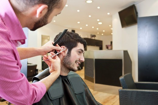 A male hairdresser cutting his male clients hair with scissors : Stock Photo