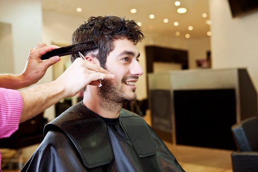 Stock Photo: 1804R-21123 A male hairdresser cutting his male clients hair with scissors