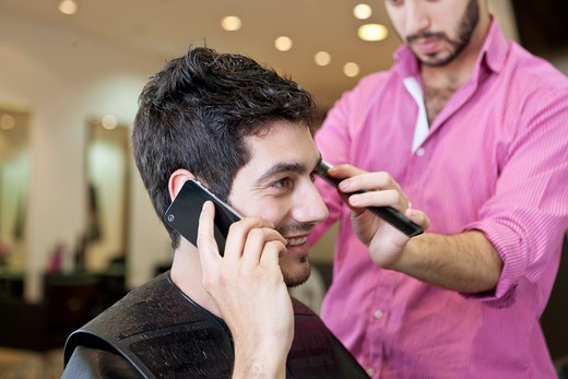 Stock Photo: 1804R-21124 A male client talking on the telephone whilst having his hair cut