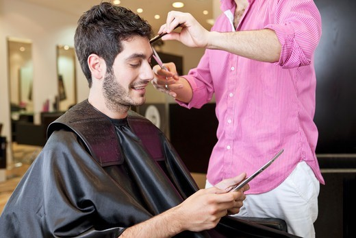 A male client looking at a digital tablet whilst having his hair cut : Stock Photo