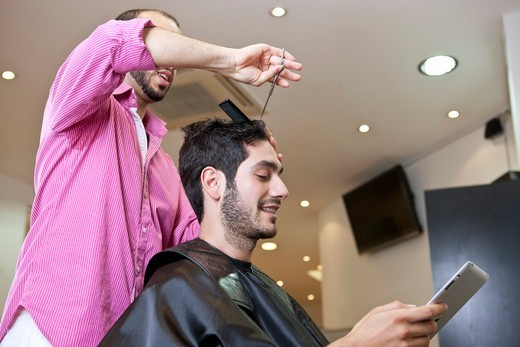 Stock Photo: 1804R-21126 A male client looking at a digital tablet whilst having his hair cut