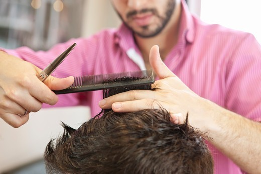 A male hairdresser cutting his male clients hair with scissors, close up : Stock Photo