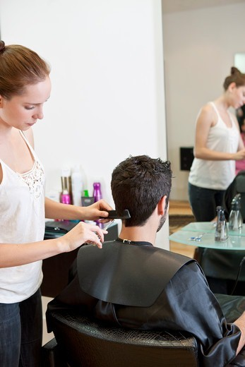 Stock Photo: 1804R-21131 A female hairdresser cutting his male clients hair with scissors