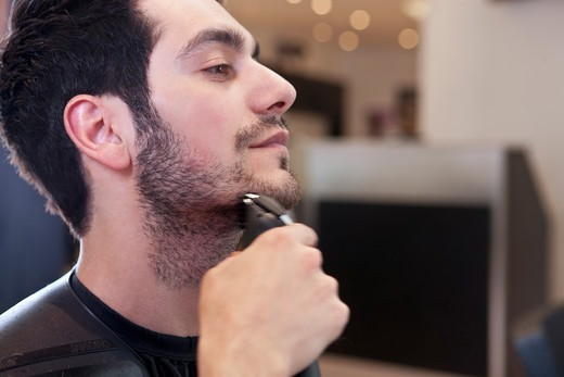 A male client having his facial hair trimmed, close up : Stock Photo