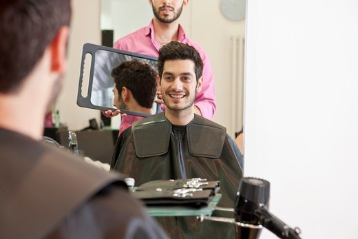 Stock Photo: 1804R-21134 A male hairdresser showing his client his new haircut in a mirror