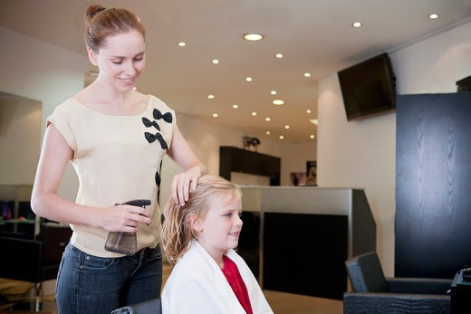 Stock Photo: 1804R-21135 A female hairdresser spraying water on a young girls hair