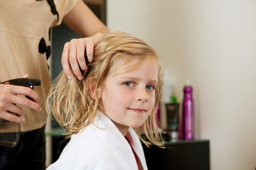 Stock Photo: 1804R-21136 A female hairdresser spraying water on a young girls hair, close up