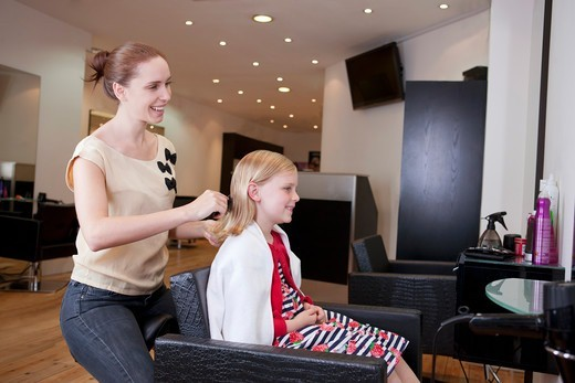 Stock Photo: 1804R-21139 A female hairdresser brushing a young girls hair in a hairdressing salon