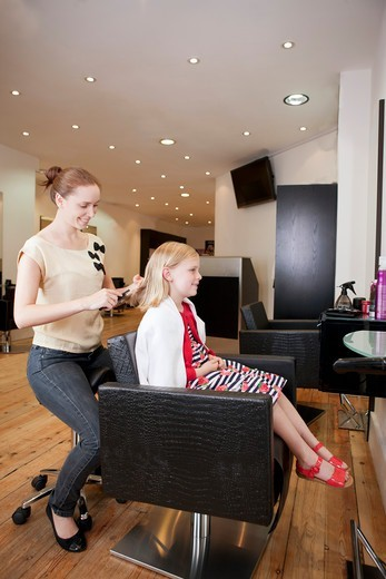 A female hairdresser brushing a young girls hair in a hairdressing salon : Stock Photo