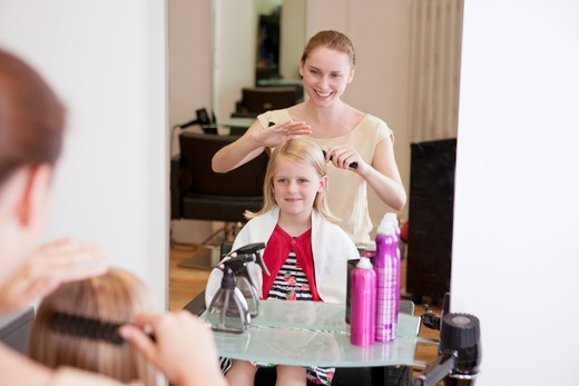 Stock Photo: 1804R-21141 A female hairdresser combing a young girls hair in a hairdressing salon