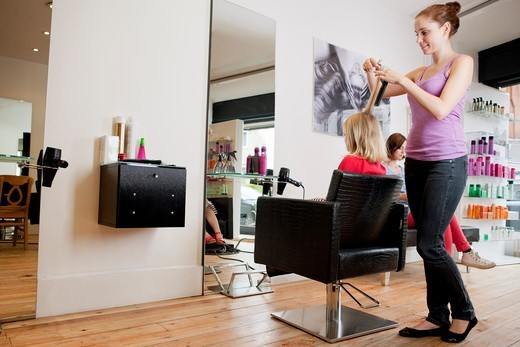 Stock Photo: 1804R-21145 A female hairdresser cutting a young girls hair in a hairdressing salon