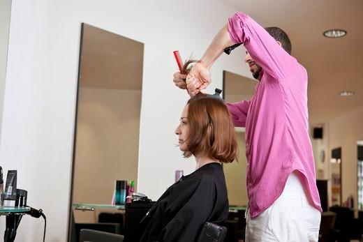 A male hairdresser preparing a female clients hair : Stock Photo