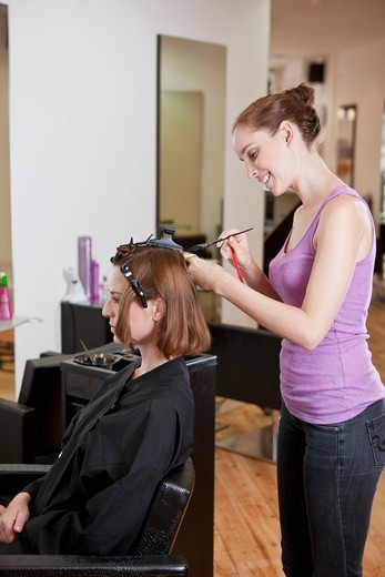 Stock Photo: 1804R-21149 A female hairdresser colouring a female clients hair