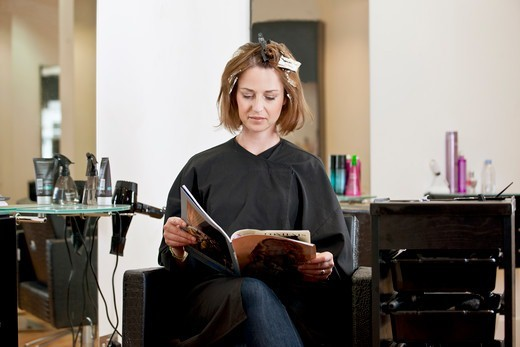 Stock Photo: 1804R-21153 A female client reading a magazine whilst she has her hair coloured in a hairdressing salon