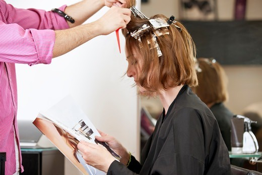 A female client reading a magazine whilst she has her hair coloured in a hairdressing salon, close up : Stock Photo