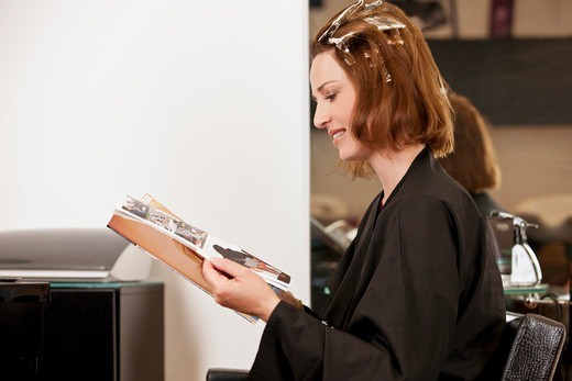 Stock Photo: 1804R-21156 A female client reading a magazine whilst she has her hair coloured in a hairdressing salon, close up