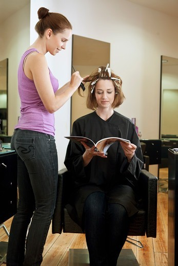 Stock Photo: 1804R-21157 A female client reading a magazine whilst she has her hair coloured in a hairdressing salon