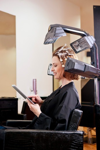 Stock Photo: 1804R-21160 A female client using an digital tablet whilst she has her hair coloured in a hairdressing salon