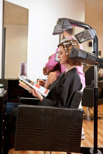 Stock Photo: 1804R-21161 A female client reading a magazine whilst she has her hair coloured in a hairdressing salon