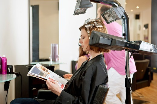 A female client reading a magazine whilst she has her hair coloured in a hairdressing salon : Stock Photo