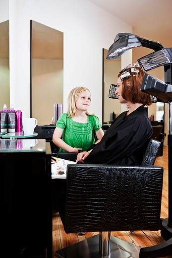 A young girl waiting in a hairdressing salon whilst her mother has her hair coloured : Stock Photo