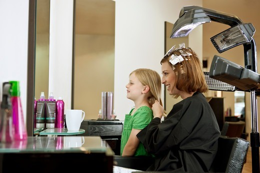 Stock Photo: 1804R-21165 Mother and daughter looking in the mirror in a hairdressing salon
