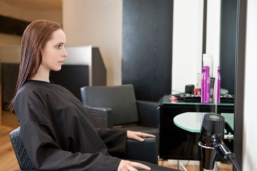 A female client looking in a mirror at a hairdressing salon : Stock Photo