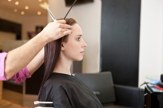 Stock Photo: 1804R-21181 A female client looking in a mirror at a hairdressing salon whilst she is having her hair cut