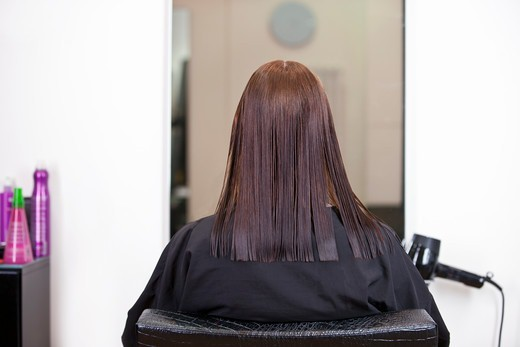 Stock Photo: 1804R-21185 A female client looking in a mirror at a hairdressing salon, view from behind