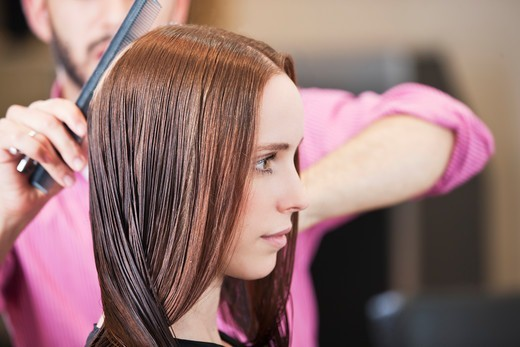A male hairdresser combing his female clients long hair : Stock Photo