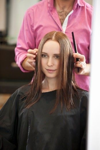 A male hairdresser cutting his female clients long hair : Stock Photo
