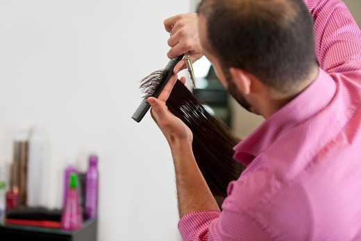 Stock Photo: 1804R-21192 A male hairdresser cutting his female clients long hair, close up