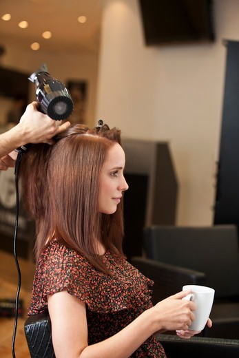 Stock Photo: 1804R-21196 A male hairdresser blow drying a female clients hair, client holding a hot beverage