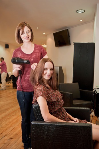A female hairdresser blow drying her female clients hair : Stock Photo