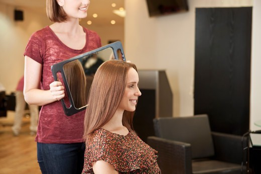 A female hairdresser showing her client her new haircut in a mirror : Stock Photo