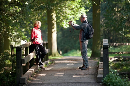 Stock Photo: 1804R-21204 A mature man taking a photograph of his partner in the countryside
