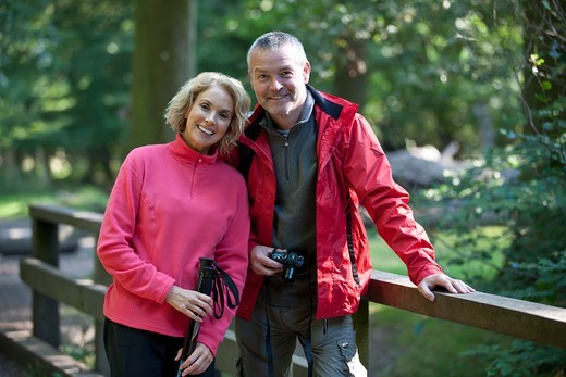 A mature couple standing on a footbridge in the countryside : Stock Photo