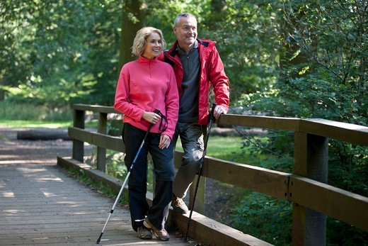 Stock Photo: 1804R-21206 A mature couple standing on a footbridge in the countryside