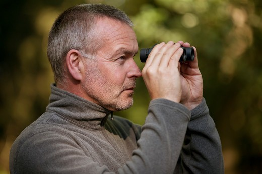 Stock Photo: 1804R-21209 A mature man looking through a pair of binoculars
