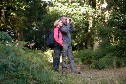 Stock Photo: 1804R-21210 A mature couple standing in the countryside, man looking through binoculars