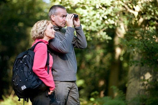 Stock Photo: 1804R-21211 A mature couple standing in the countryside, man looking through binoculars