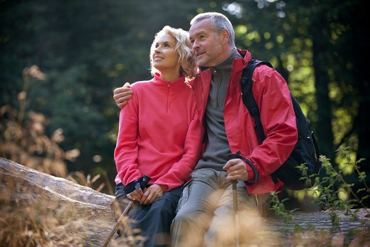 Stock Photo: 1804R-21214 A mature couple sitting on a tree trunk looking at their surroundings