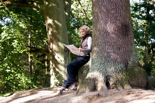 Stock Photo: 1804R-21221 A mature woman resting on a tree, looking at a map