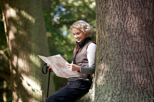 Stock Photo: 1804R-21222 A mature woman resting on a tree, looking at a map, close up