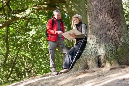Stock Photo: 1804R-21223 A mature couple standing in woodland looking at a map