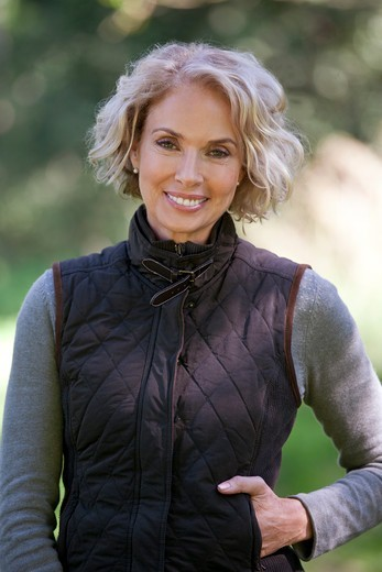 A portrait of a mature woman standing outdoors, smiling : Stock Photo
