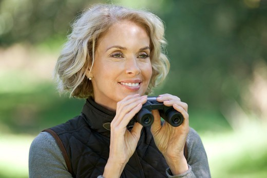 A mature woman outdoors, holding a pair of binoculars : Stock Photo