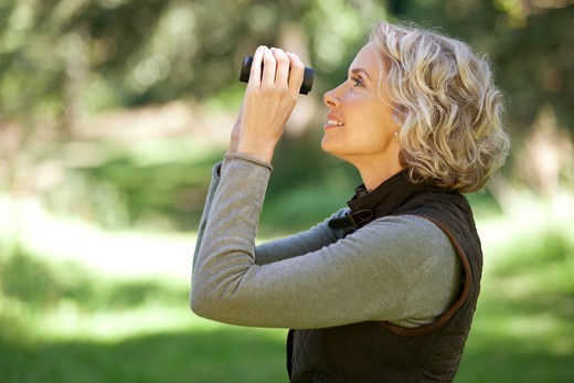 Stock Photo: 1804R-21235 A mature woman outdoors, looking through a pair of binoculars