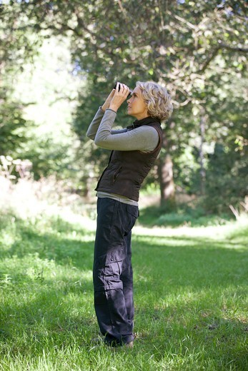 Stock Photo: 1804R-21237 A mature woman outdoors, looking through a pair of binoculars