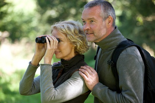 A mature couple outdoors, woman looking through a pair of binoculars : Stock Photo